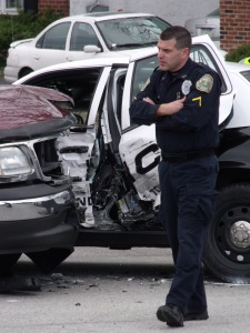 The officer who was driving the police car at the time of the accident William Gershanick walk away from examining the crash scene. (Tom Sofield)